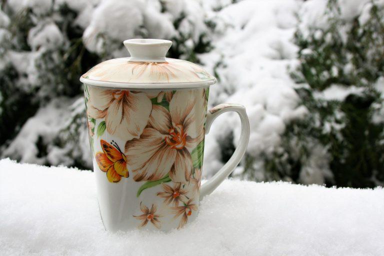 Imagem de caneca de porcelana com tampa e estampa florida sobre superfície nevada