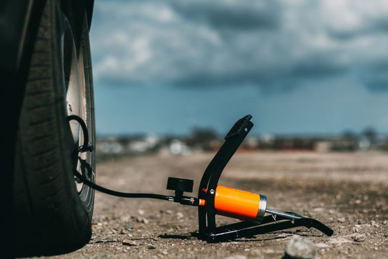 Um compressor portátil enchendo um pneu de carro em uma estrada de terra e pedras.