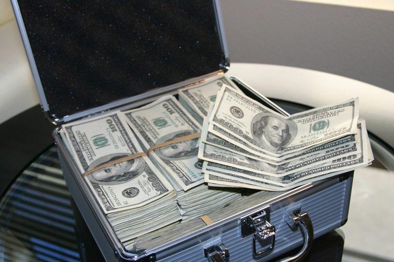 Uma maleta com maços de notas organizadas e algumas cédulas soltas presentes mais acima