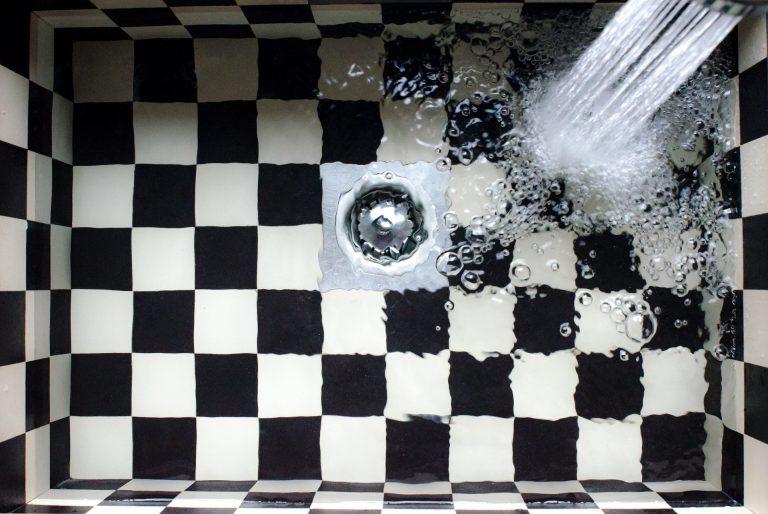Uma pia xadrez entupida e uma torneira ligada.