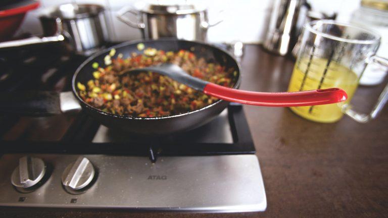 Imagem de espátula de silicone preta com cabo vermelho sobre panela com alimentos