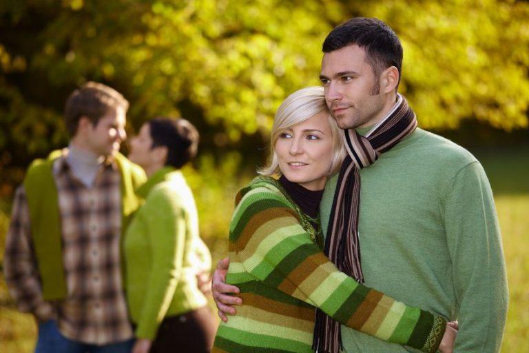 Foto de um casal abraçado usando roupas de frio em um lugar aberto. O homem usa uma faixa de cabelo e dreads pendurados. A mulher usa um cachecol.
