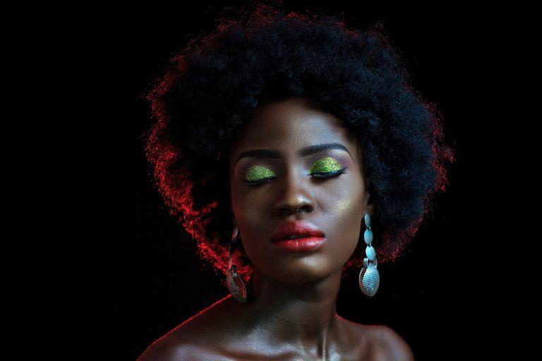 Foto de uma mulher negra, com cabelo afro, brincos grandes e maquiagem chamativa. Ela está em um local com fundo preto e usa iluminador dourado no rosto.