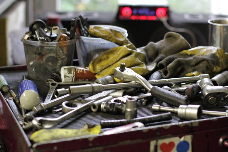 Um estojo de ferramentas aberto, repleto de chaves, soquetes manuais e de impacto. Também há um par de luvas sujas e dois potes com soquetes e parafusos.
