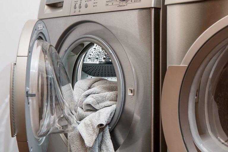 Imagem de máquina de lavar roupas aberta com toalhas penduradas