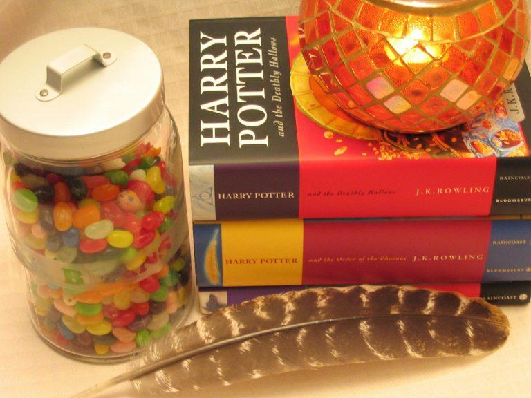 Dois livros do Harry Porter, um em cima do outro, acima dos livros há uma bola de cristal colorida. Ao lado existe um pote fechado de vidro com balas coloridas.