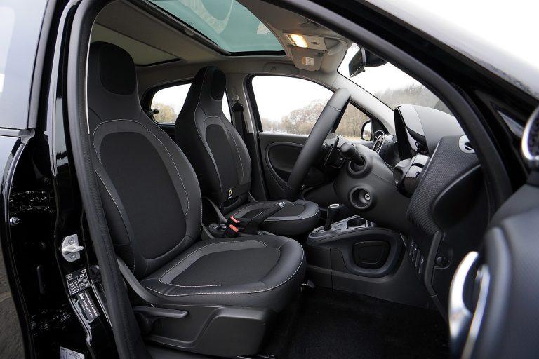 A imagem mostra parte do interior automotivo com bancos da frente, painel, console central, câmbio de marcha e volante.