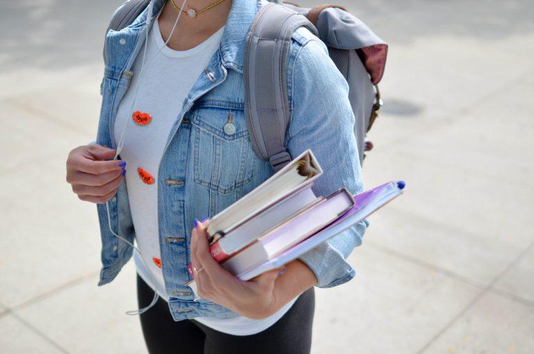 Imagem de uma estudante carregando o material escolar.