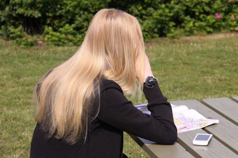 Uma mulher lendo uma revista em cima de uma mesa