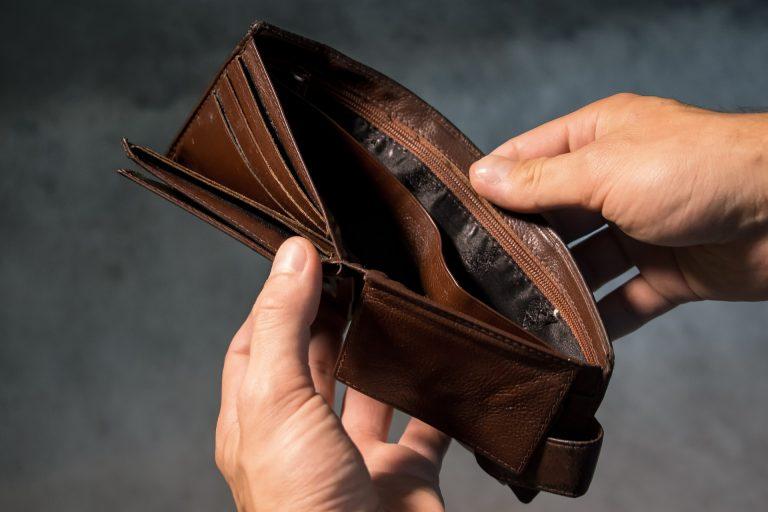 Uma carteira aberta e vazia nas mãos de uma pessoa