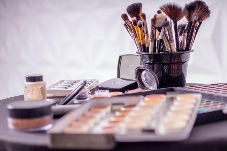 Foto de uma bancada cheia de maquiagens, como paletas de sombras, bases, pós, com destaque a um baldinho cheio de pinceis, entre eles, o pincel leque.