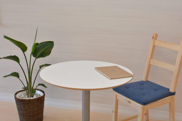 Foto de uma mesa redonda, com um notebook fechado em cima, e, do lado direito, uma cadeira com assento azul. Do lado esquerdo, uma planta em um vaso diretamente no chão.