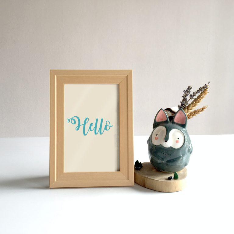 Imagem de porta-retratos de madeira com inscrição em inglês e uma peça decorativa de anima de cerâmica ao lado