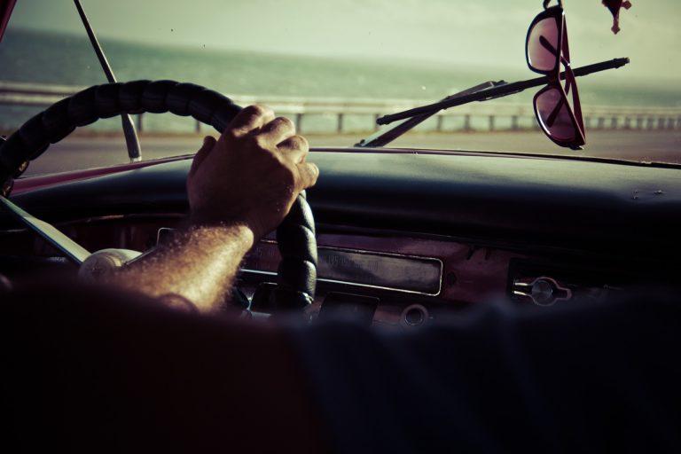 Uma mão em cima do volante de um carro