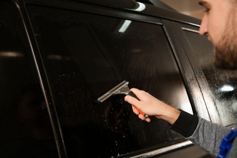 Um homem limpando o espelho do carro com rodo