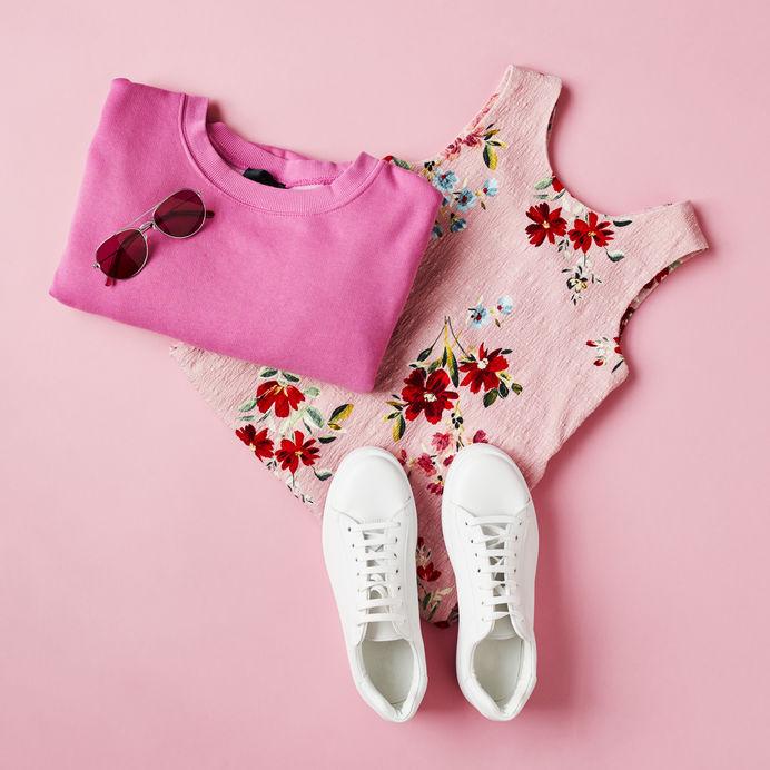 sapato branco ao lado da blusa e camisa rosa e óculos de sol