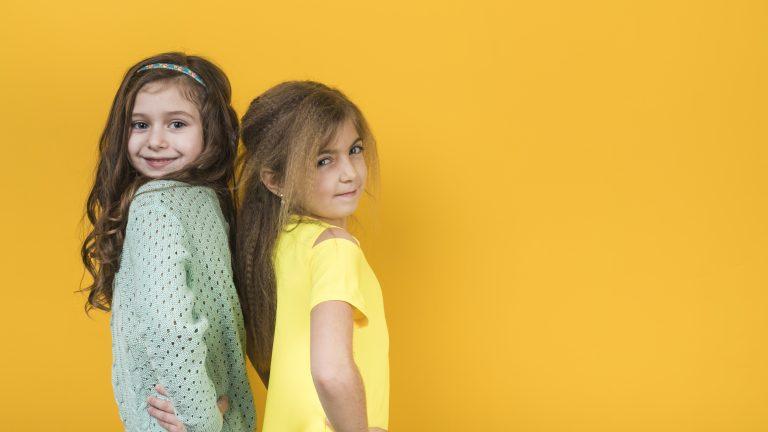 Duas meninas uma de costas para a outra com a mão na cintura e fazendo pose