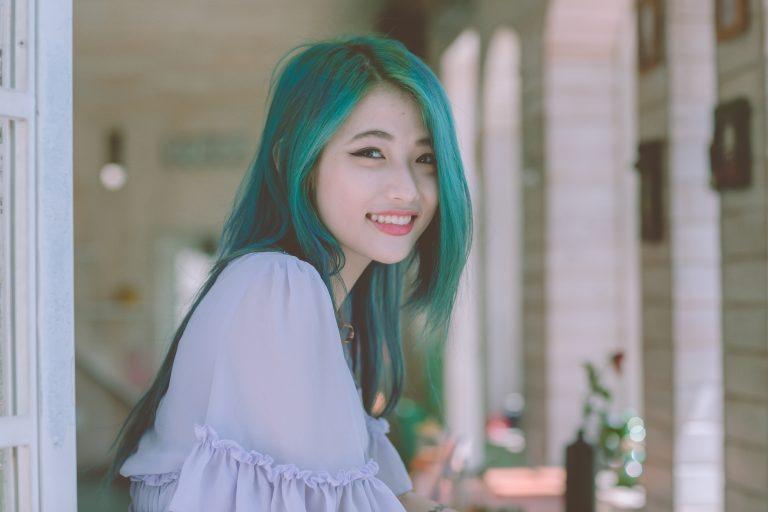 Foto de uma moça oriental de lado, com o rosto virado para frente, sorrindo, com um longo cabelo verde azulado.