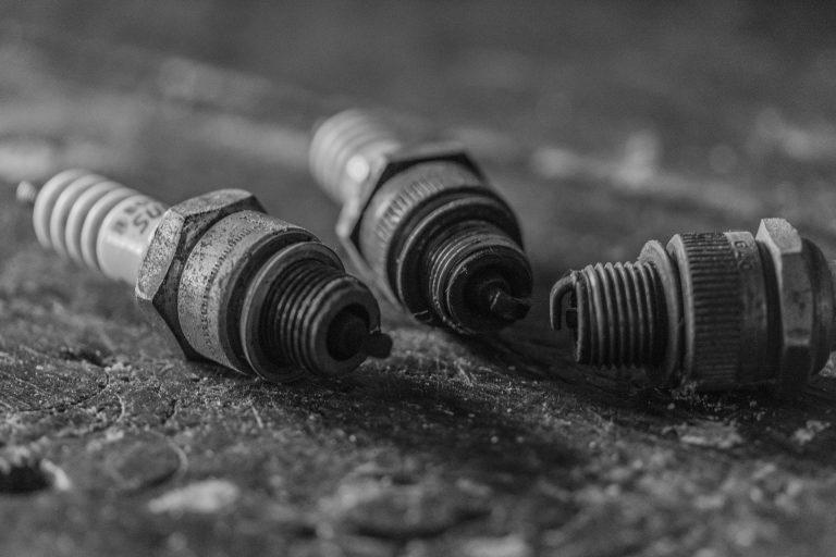 3 velas de ignição usadas em cima de um chão de cimento.