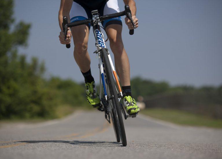 Detalhe de ciclista sobre bicicleta com bermuda.