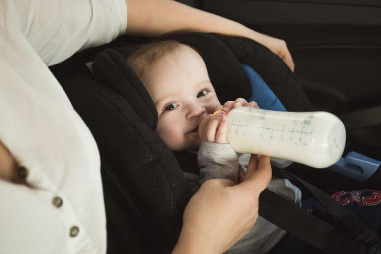 Bebê no bebê conforto dentro do carro tomando mamadeira.