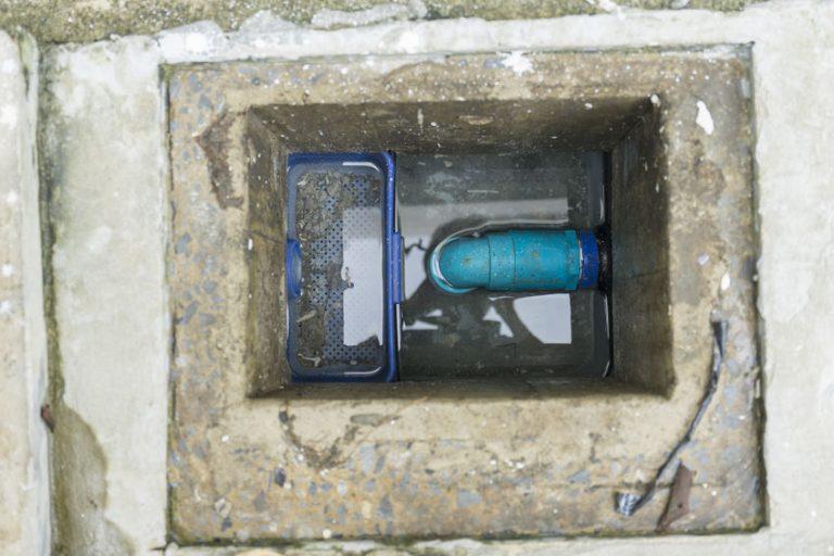 Imagem mostra uma caixa de gordura construída em concreto aberta.