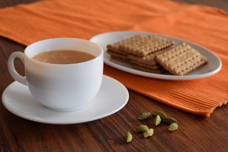 Xícara de chá com biscoito ao lado, e grãos de cardamomo sobre a mesa.