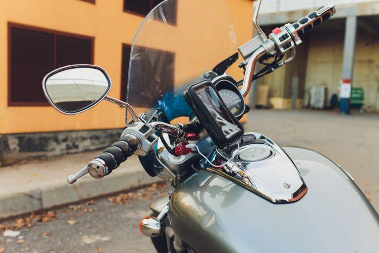 Imagem mostra uma motocicleta com um carregador preso ao guidão.