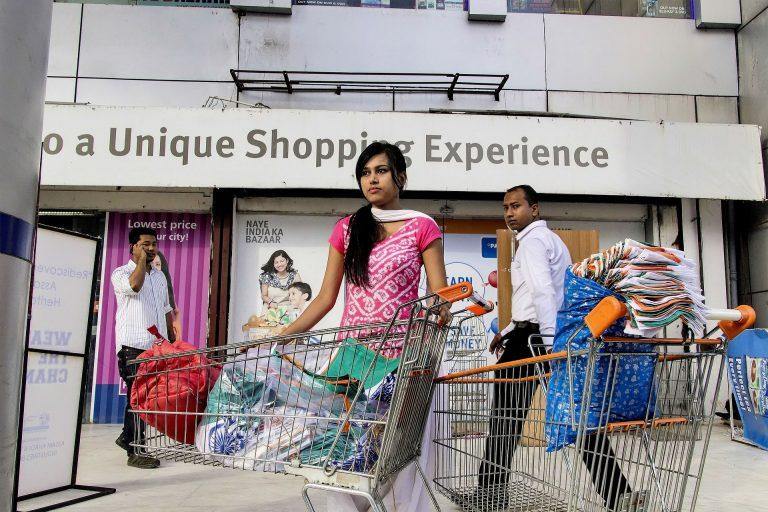 Imagem de pessoas carregando carrinhos de compra de supermercado