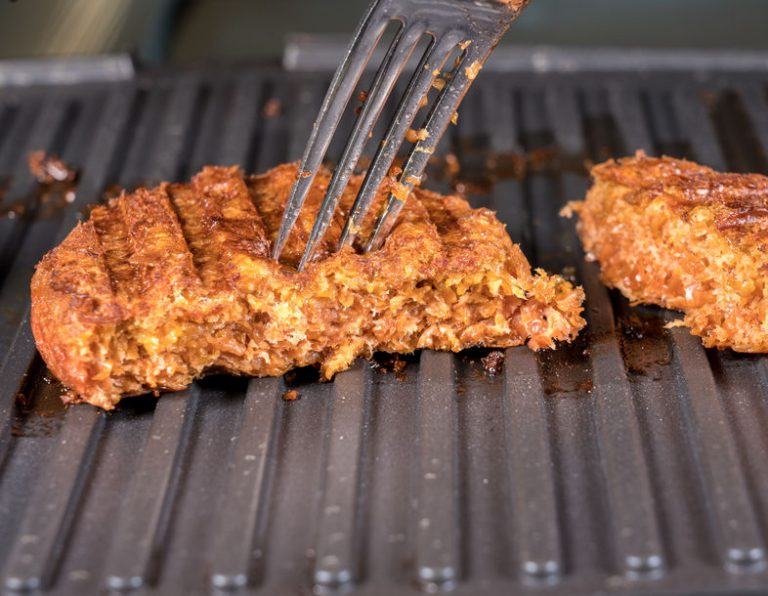 Imagem mostra uma carne vegetal sendo cozida em uma chapeira.