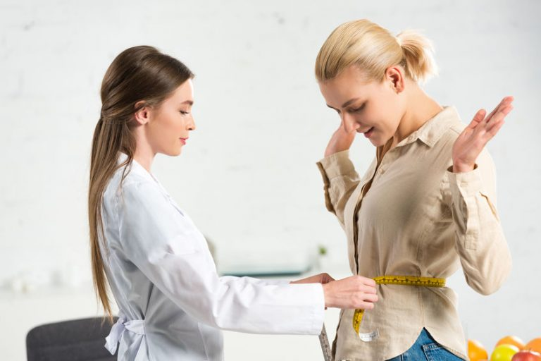 Médica mede cintura de mulher com auxílio de fita métrica