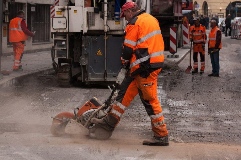 Imagem mostra um homem trabalhando na construção civil e usando colete refletivo.