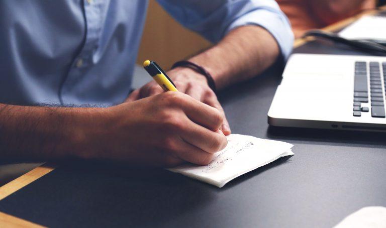 Homem fazendo anotações com notebook à frente.