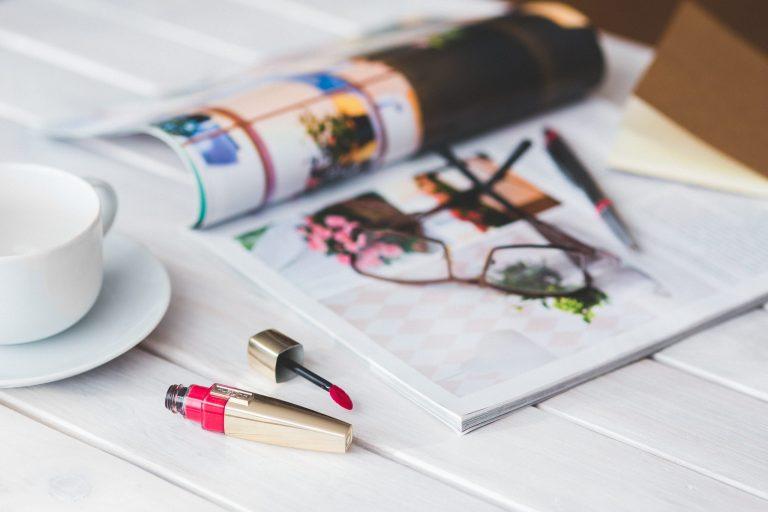 Lip tint sobre mesa com revistas, óculos e xícara ao lado.