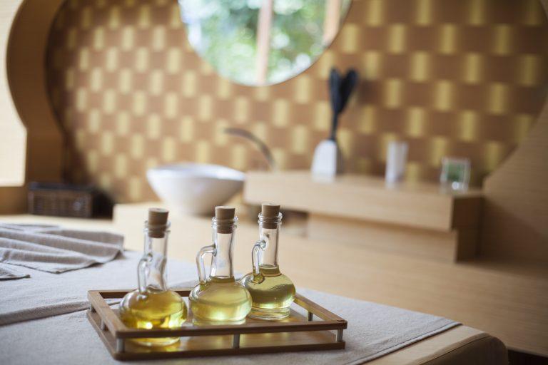 Foto de três vidros de algum óleo em um ambiente que parece um banheiro.