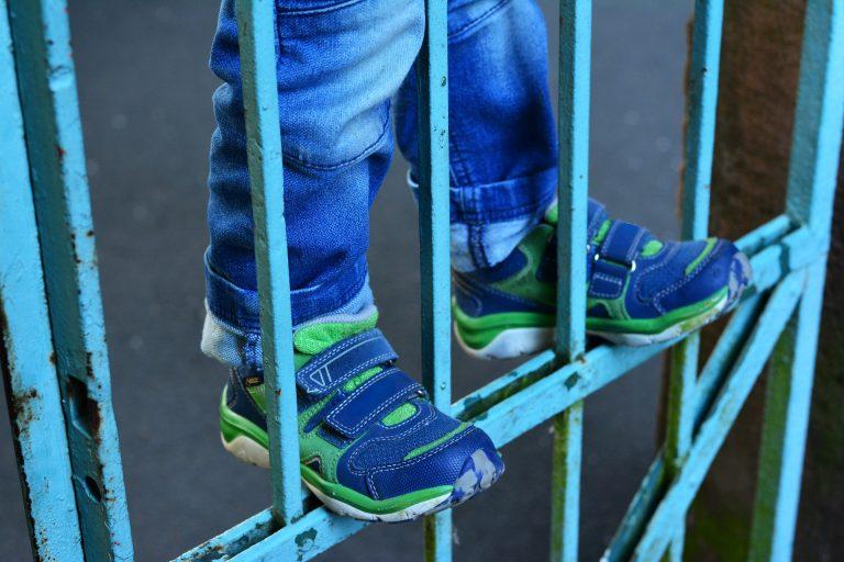Imagem mostra uma criança pendurada em uma grade com destaque para as pernas e os pés com tênis.