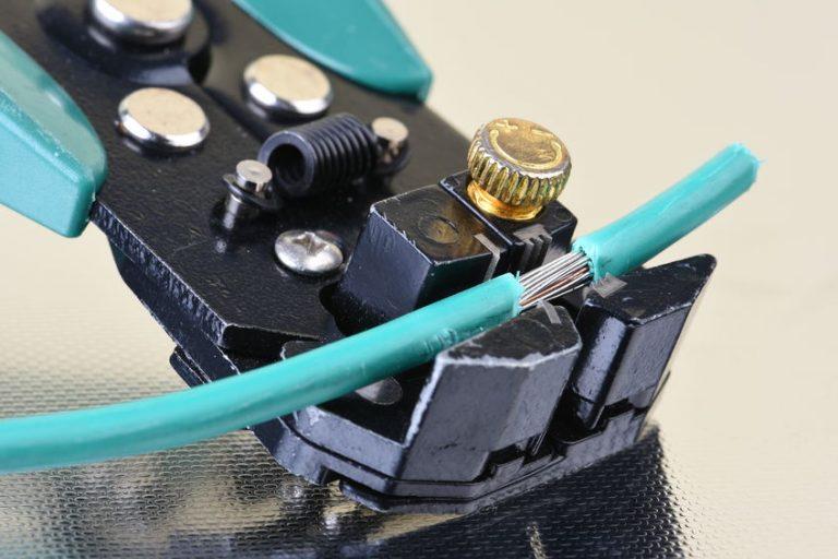 Um alicate desencapador com ganchos desencapando uma pequena parte de um fio.