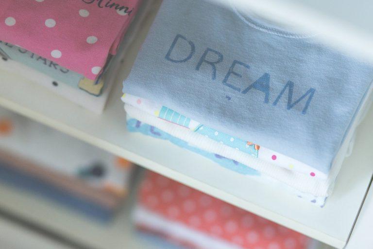 Imagem de roupas infantis empilhadas em prateleiras
