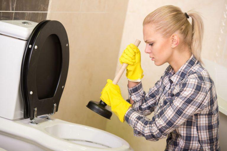 Uma mulher com luvas usando um desentupidor pequeno para desentupir vasos sanitários.