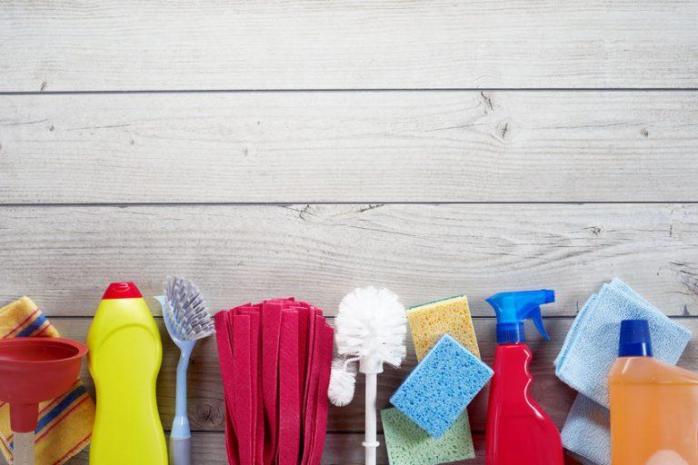 Uma escova sanitária no meio. Na esquerda e à direita há outros materiais de limpeza de banheiro.