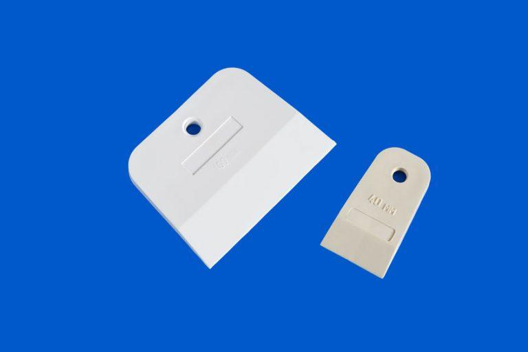 Imagem de espátula de silicone branca com cabo de madeira junto com pães e outros utensílios de cozinha