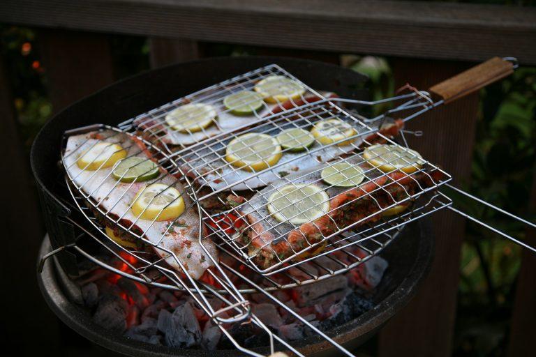 Duas grelhas para peixe na churrasqueira. Em uma grelha há um peixe. Na outra grelha existem três peixes.