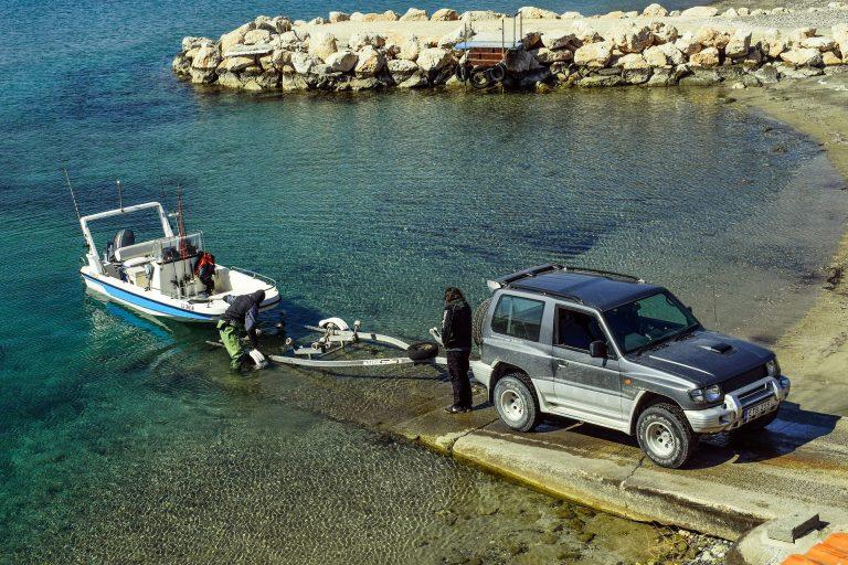 Um carro rebocando um barco que está saindo da água.