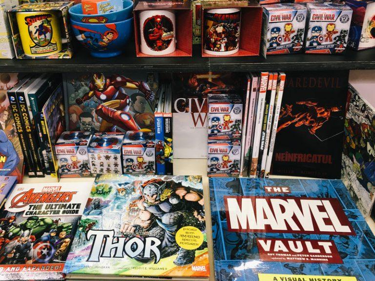 Diversos HQs Marvel e DC organizados em prateleiras de uma loja.