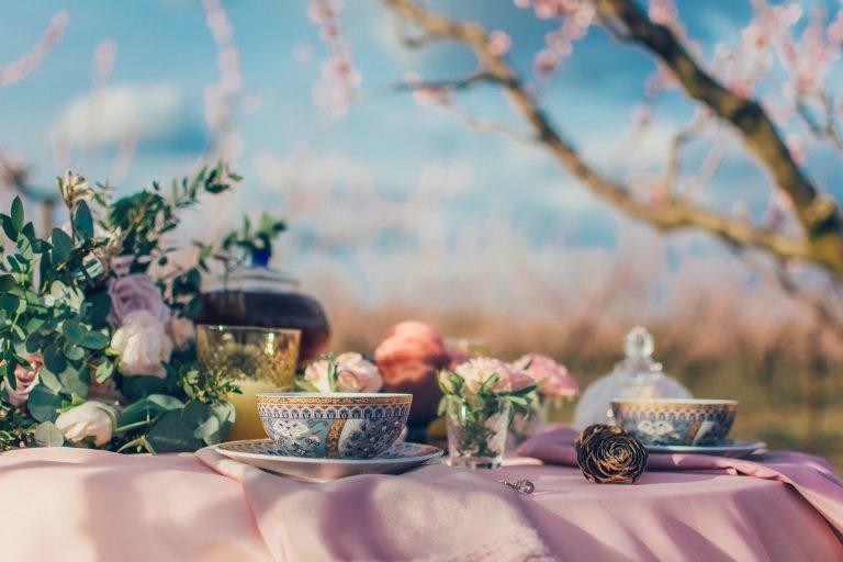 Imagem de mesa com flores e jogo de chá com várias peças de porcelana decorada