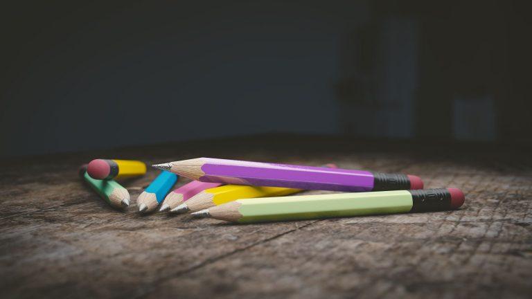 Sete lápis coloridos comuns com ponta de borracha em um piso rústico.