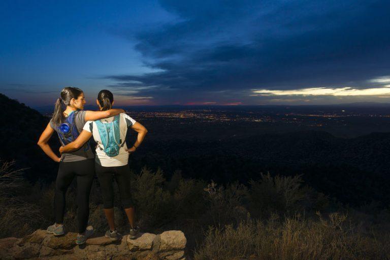 Imagem de duas mulheres observando a noitecer com mochilas de hidratação