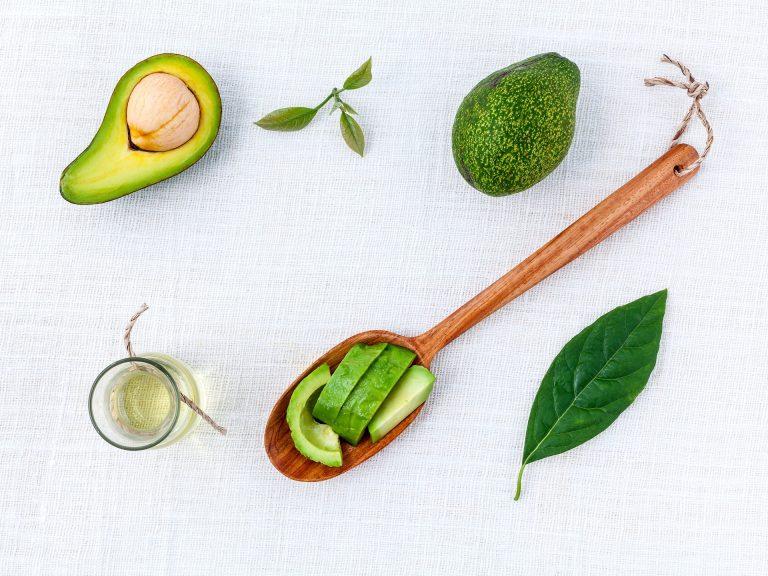 Imagem de óleo de abacate ao lado de vários tipos de cortes da fruta