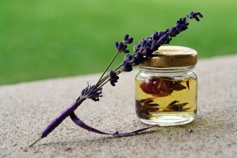 Foto de um pequeno potinho com óleo amarelo e uma flor em seu interior, ao lado de um ramo de lavanda. Ao fundo, um gramado bem verde.