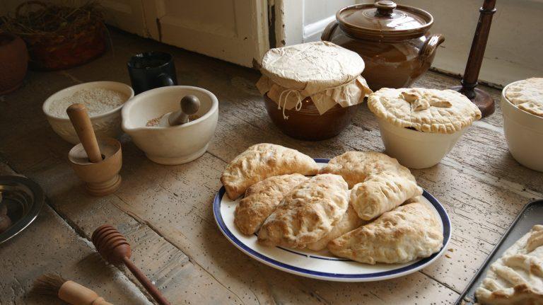 Imagem de pilão de madeira e pilão de cerâmica ao lado de prato com pães